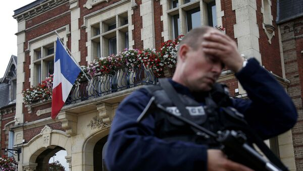 A policeman reacts as he secures a position in front of the city hall after two assailants had taken five people hostage in the church at Saint-Etienne-du -Rouvray near Rouen in Normandy, France, July 26, 2016 - Sputnik International