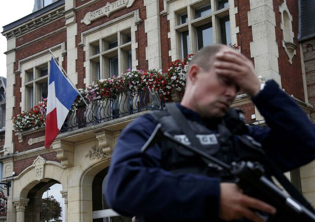 A policeman reacts as he secures a position in front of the city hall after two assailants had taken five people hostage in the church at Saint-Etienne-du -Rouvray near Rouen in Normandy, France, July 26, 2016