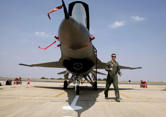 U.S. Air Forces F-16 demonstration team pilot, Ryan Worrell from Iowa, walks past the F-16, a fighter aircraft, on display on the fourth day of the Aero India 2013 at Yelahanka air base in Bangalore, India, Saturday, Feb. 9, 2013