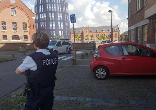 A photo taken with a mobile phone on August 6, 2016, shows a police officer standing guard close to a police building in the southern Belgian city of Charleroi following a machete attack