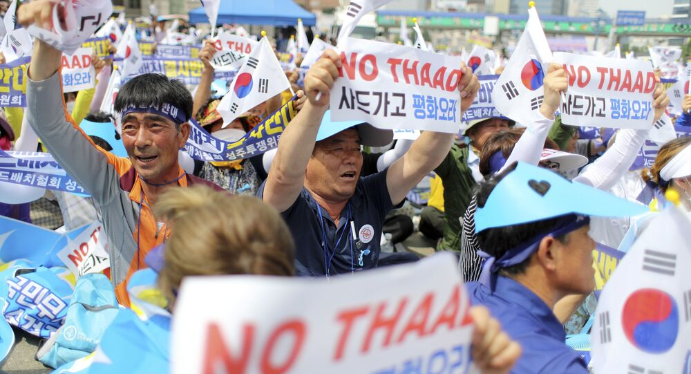 Residents in a rural South Korean town shout slogans in protest of a plan to deploy an advanced U.S. missile defense system called Terminal High-Altitude Area Defense, or THAAD, in their neighborhood, in Seoul, South Korea, Thursday, July 21, 2016