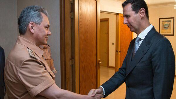 Russian Defense Minister Sergei Shoigu, left, and President of Syria Bashar al-Assad at a meeting in Syria - Sputnik International