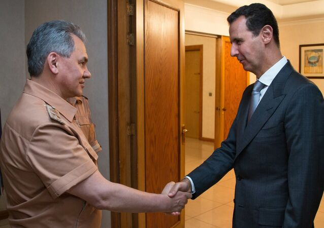 Russian Defense Minister Sergei Shoigu, left, and President of Syria Bashar al-Assad at a meeting in Syria