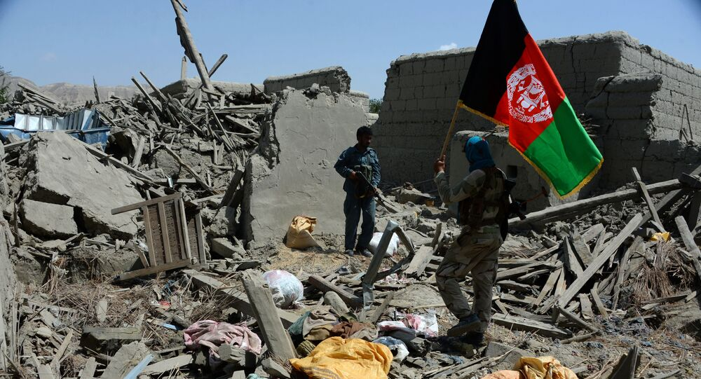 Afghan security force member walks holding the Afghan national flag after government forces took full control of a village from Daesh during a military operation in Kot District of eastern Nangarhar province (File)
