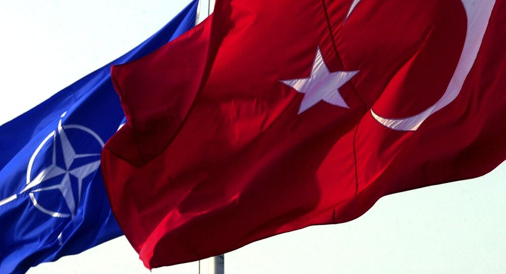 A Turkish flag waves in front of NATO's one
