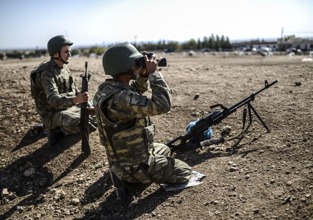 A Turkish soldier uses binoculars to check the Syrian border near the Mursitpinar border crossing on the Turkish-Syrian border in the southeastern town of Suruc, Sanliurfa province, on October 4, 2014
