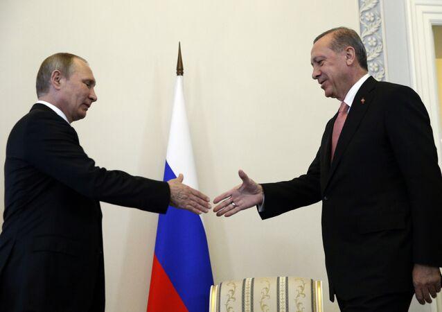 Russian President Vladimir Putin, left, welcomes Turkish President Recep Tayyip Erdogan in the Konstantin palace outside St.Petersburg, Russi
