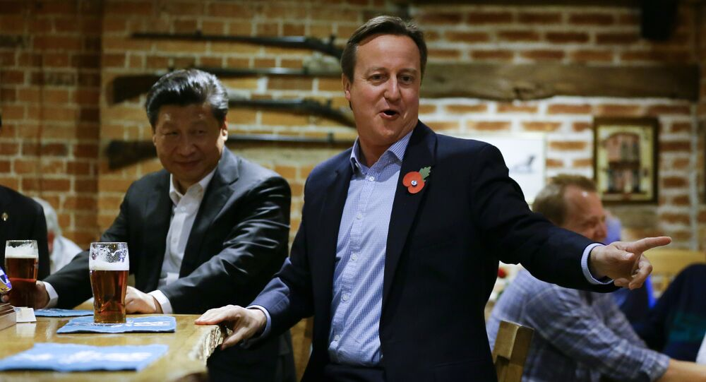 British Prime Minister David Cameron (R) gestures as he drinks a pint of beer with Chinese President Xi Jinping at a pub in Princess Risborough near Chequers, northwest of London, on October 22, 2015