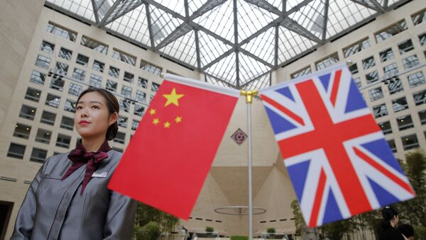 A member of staff stands behind flags as officials arrive for the UK-China High Level Financial Services Roundtable at the Bank of China head office building in Beijing on July 22, 2016 - Sputnik International
