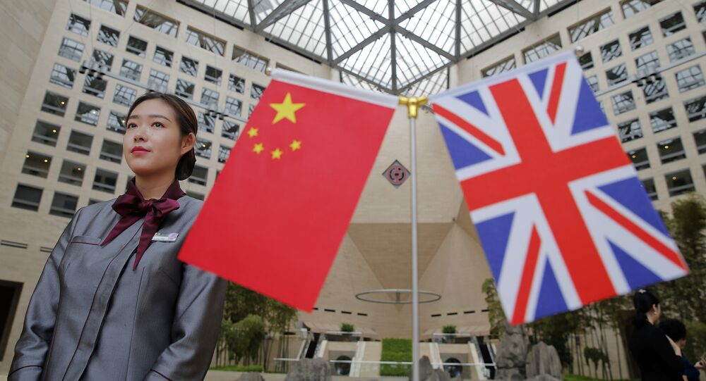 A member of staff stands behind flags as officials arrive for the UK-China High Level Financial Services Roundtable at the Bank of China head office building in Beijing on July 22, 2016