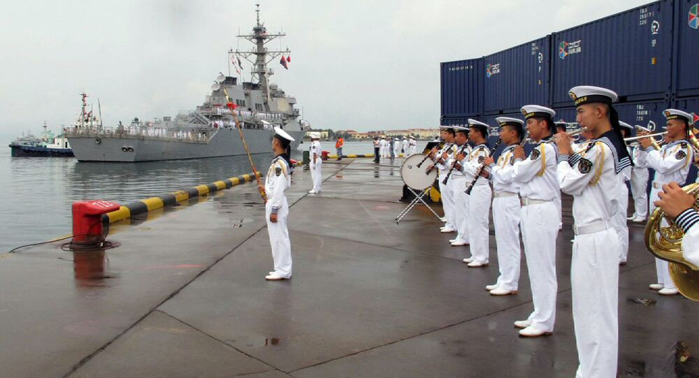 A Chinese military band plays as the guided missile destroyer USS Benfold arrives in port in Qingdao.