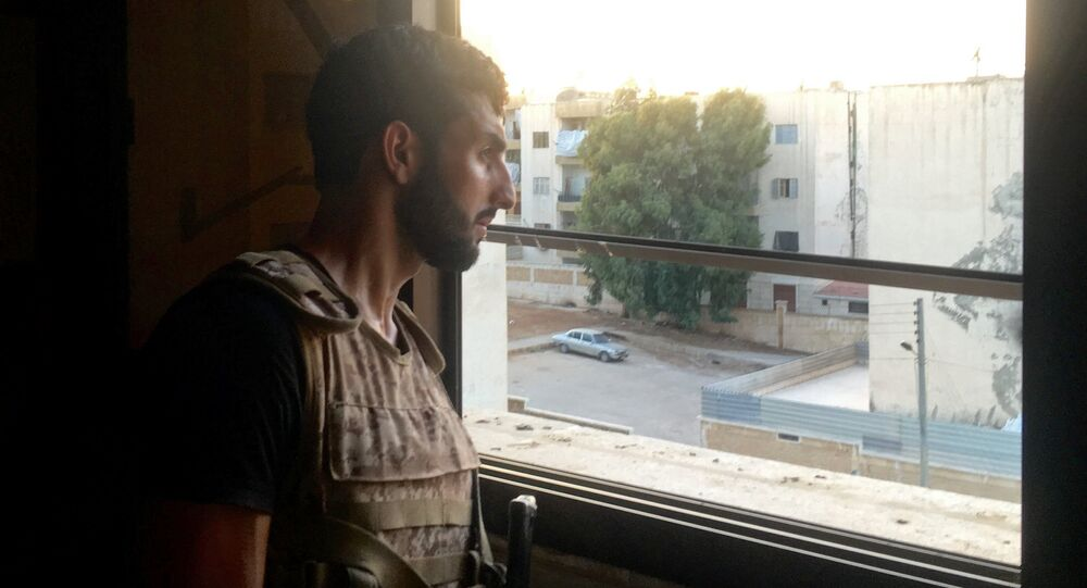 A Syrian Army soldier examines a position from an apartment window in southern Aleppo