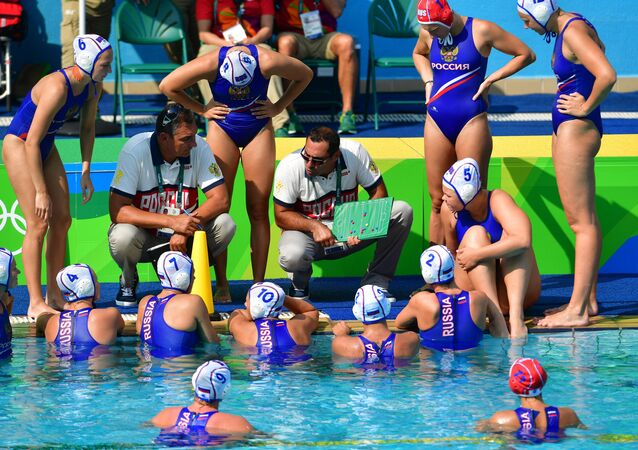 The Russian team's head coach Alexander Gaidukov, right, and the team players during the break in the А group match in women's water polo at the XXXI Summer Olympics