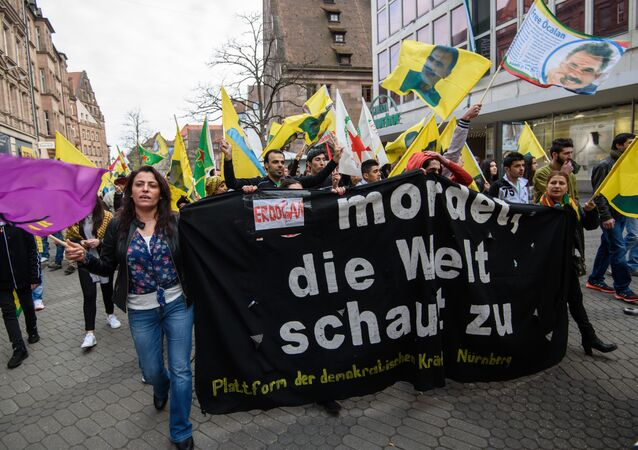Kurdish supporters demonstrate with a banner 'Erdogan kills. The world is watching' on April 10, 2016 in Nürnberg