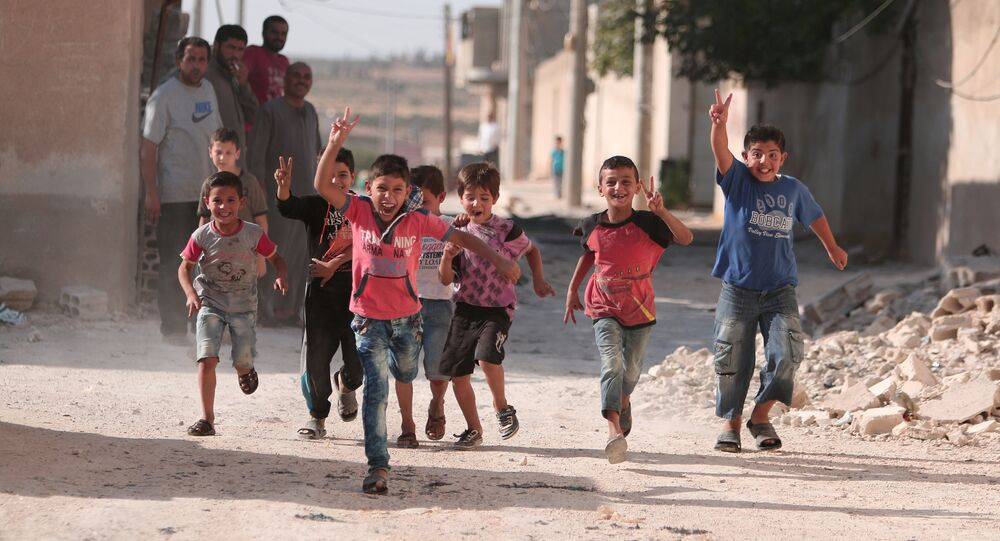 Children flash victory signs as they play in Manbij, in Aleppo Governorate, Syria, August 9, 2016