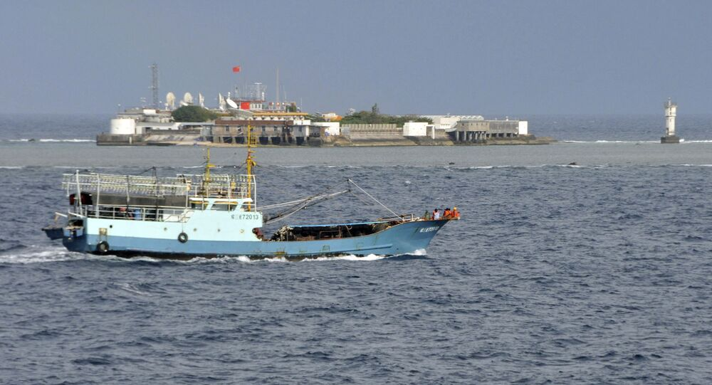 Chinese fishing vessel sails by Fiery Cross Reef, background, also known as Yongshu Reef, of the Spratly Islands in South China Sea. File photo.