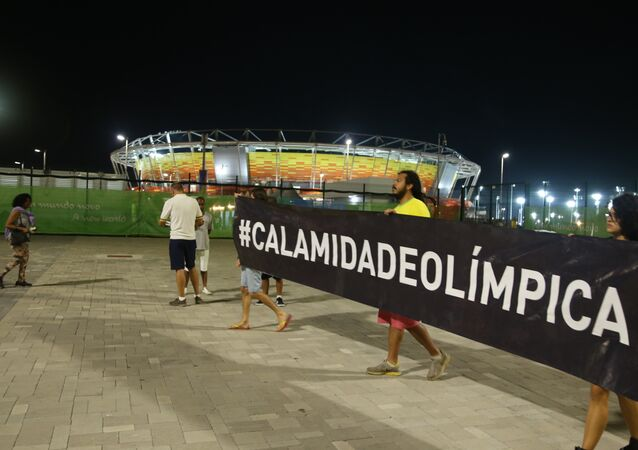 Protesters carry banner with a #Calamidadeolímpica hashtag (#OlympicCalamity).