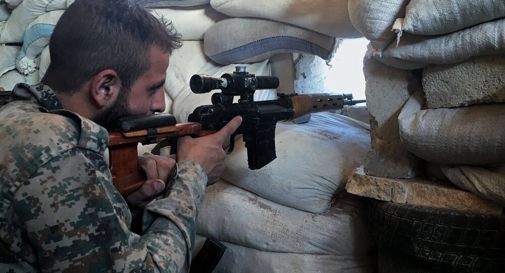 Syria. A Syrian Army soldier at the front line against a military logistics school in southern Aleppo