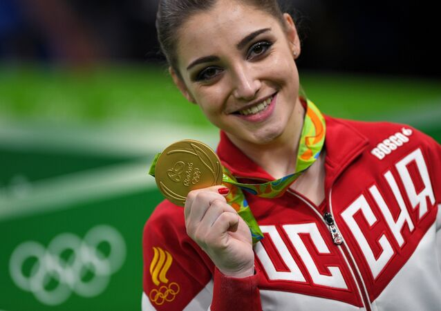 Aliya Mustafina (Russia), winner of the gold medal in the uneven bars event of the women's artistic gymnastics competition at the XXXI Summer Olympics, during the medal ceremony