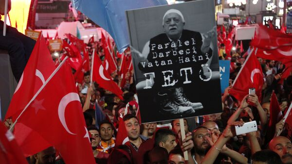 Supporters of Turkish President Recep Tayyip Erdogan wave their national flags and hold a portrait of Fethullah Gulen, a U.S.-based Muslim cleric with Turkish words that read: the Coup nation traitor, FETO (Feto is the nickname of Fethullah Gulen), during a pro-government rally at Kizilay main square, in Ankara, Turkey, Wednesday, July 20, 2016 - Sputnik International