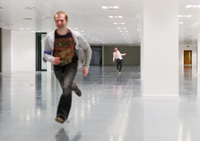 A zombie actor chases a man during a zombie game