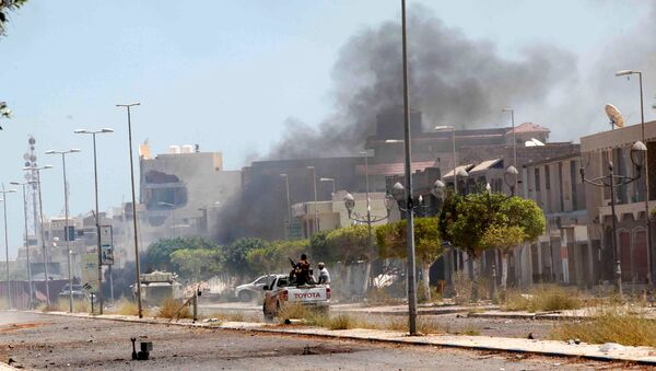 Fighters ride a pickup truck as smoke rises during a battle with Islamic State fighters in neighborhood Number Two in Sirte, Libya - Sputnik International