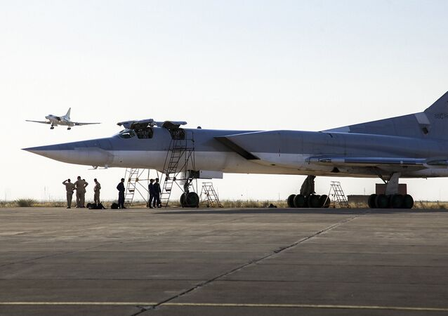 In this photo taken on Monday, Aug. 15, 2016, a Russian Tu-22M3 bomber stands on the tarmac while another plane lands at an air base near Hamedan, Iran.