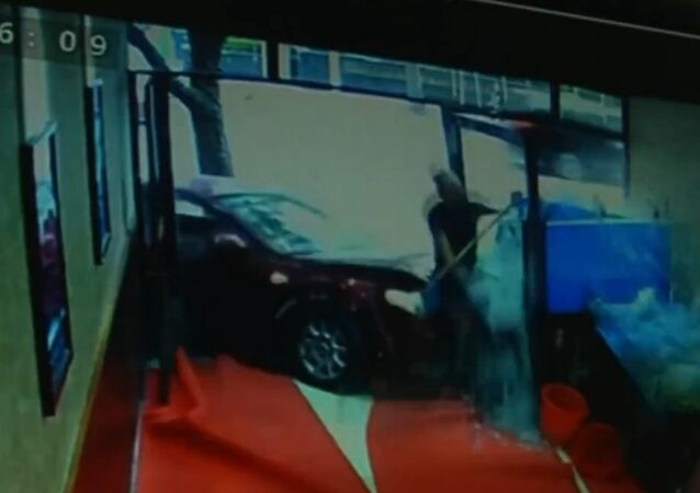 Car crashes into shop window knocking down cleaner