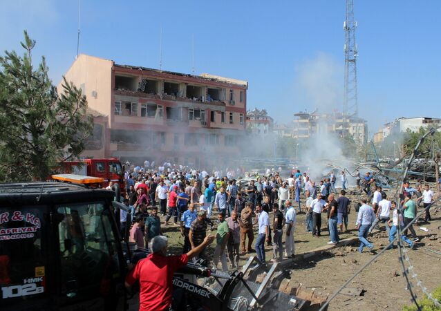 People rush to the blast scene after a car bomb attack on a police station in the eastern Turkish city of Elazig, Turkey