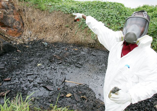 A civil protection member of Ivory Coast points at a site polluted with toxic waste at the Akouedo district in Abidjan 19 September 2006. In mid-August the Probo Koala ship unloaded in Abidjan more than 500 tonnes of a highly toxic mixture of oil residue and caustic soda used to rinse out the ship's tanks. The poisons are known to cause nausea, rashes, fainting, diarrhoea and headaches. Besides the seven deaths, 24 people are still hospitalized and more than 37,000 have sought medical treatment.
