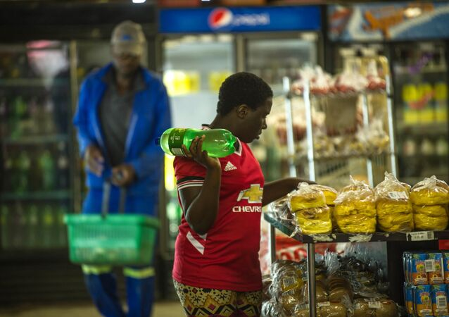 A woman holds a bottle of soft drink as she shops around at a local supermarket in the Township of Zandspruit, Greater Johannesburg, South Africa, on March 15, 2016