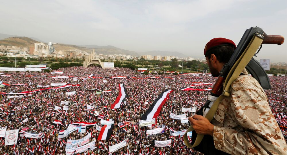 A soldier looks at people rallying to show support to a political council formed by the Houthi movement and the General People's Congress party to unilaterally rule Yemen by both groups, in the capital Sanaa August 20, 2016