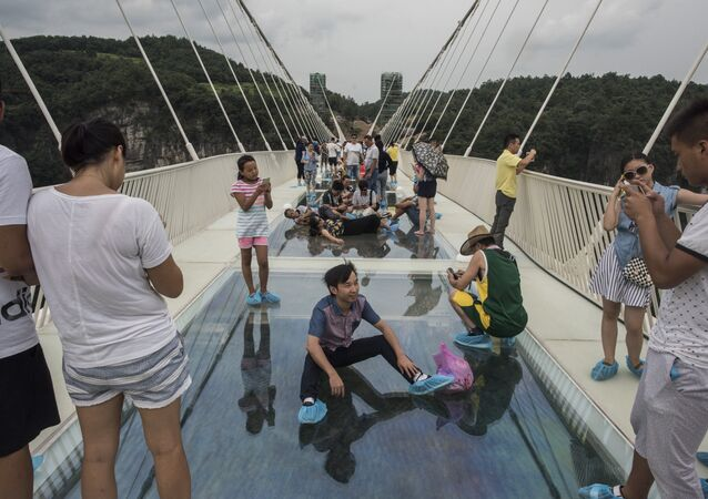 A tourist poses for a photograph on the world's highest and longest glass-bottomed bridge above a valley in Zhangjiajie in China's Hunan Province on August 20, 2016