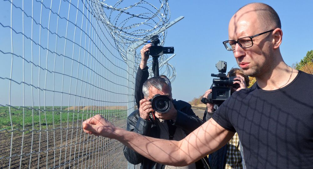 Ukrainain Prime Minister Arseniy Yatsenyuk (R) touches a piece of gate as he visits a newly constructed section of the Ukrainian-Russian border, near the Goptivka border crossing, north of Kharkiv, eastern Ukraine, on October 15, 2014