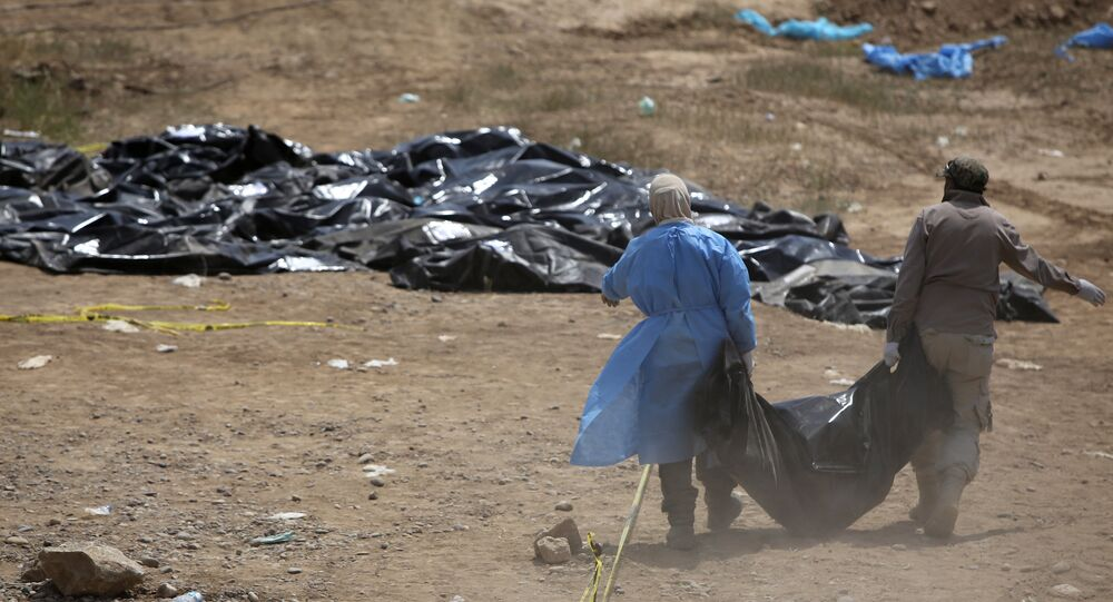 Members of the Iraqi security forces work at the site of a mass grave containing the remains of people believed to have been slain by jihadists of the Islamic State (IS) group at the Speicher camp in the city of Tikrit, on April 12, 2015