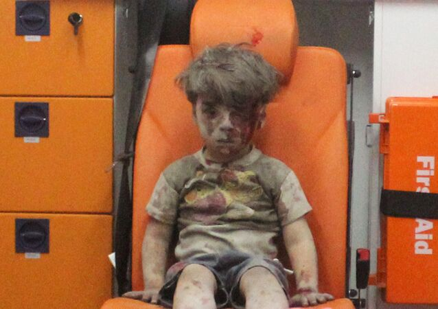 Five-year-old Omran Daqneesh, with bloodied face, sits inside an ambulance after he was rescued following an airstrike in the rebel-held al-Qaterji neighbourhood of Aleppo, Syria August 17, 2016.
