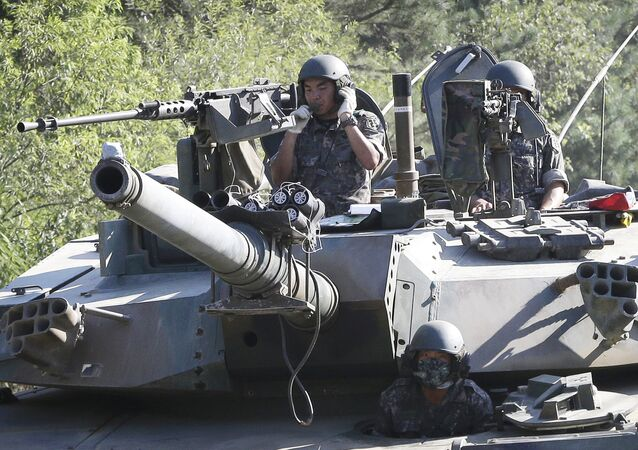 South Korean army soldiers ride a K-1 tank during the annual exercise in Paju, South Korea, near the border with North Korea