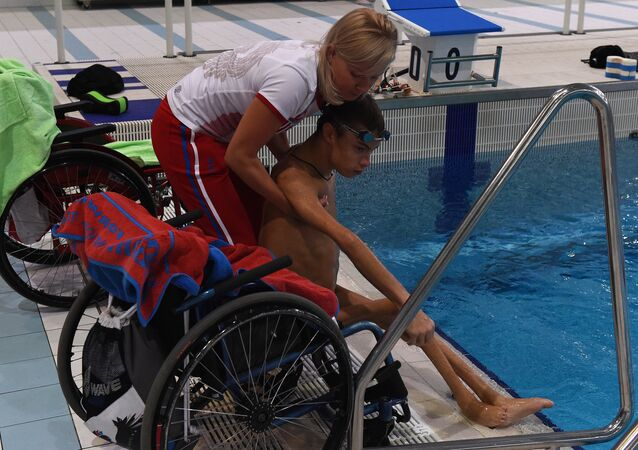 The coach Olesya Alexandrova helps paralympic swimmer Alexander Makarov, member of Russia's Paralympic national team, after a training session in the town of Ruza, 100 km west of Moscow, on August 18, 2016