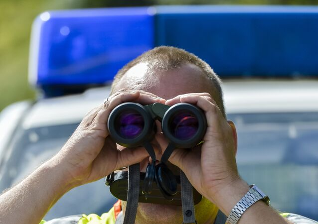 A police officer uses binoculars at a check point during control on the border crossing between Austria and Germany at the southern German city of Kiefersfelden on September 16, 2015