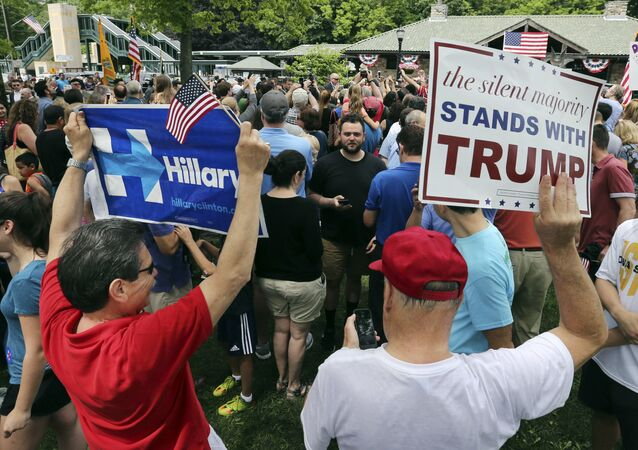 A supporter of Democratic presidential candidate Hillary Clinton and a Republican presidential candidate Donald Trump supporter hold signs as they attend a Memorial Day parade Monday, May 30, 2016, in Chappaqua, N.Y. Clinton and her husband former President Bill Clinton, along with New York Gov. Andrew Cuomo, walked in the parade