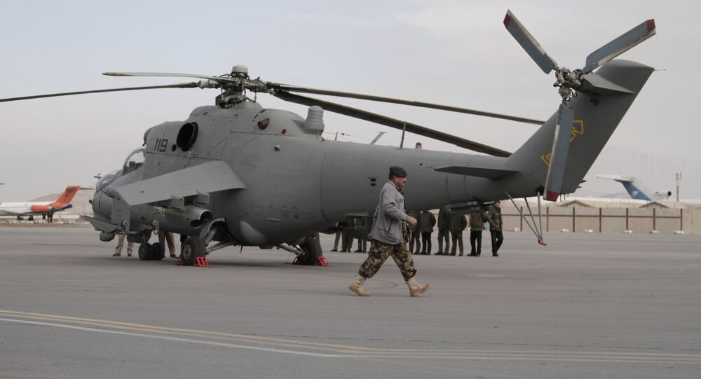 An Afghan soldier walks past Indian donated helicopters to Afghanistan at the Kabul airport in Kabul, Afghanistan, Friday, Dec. 25, 2015