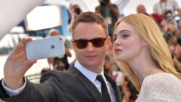 Danish director Nicolas Winding Refn (L) and US actress Elle Fanning pose for a selfie on May 20, 2016 during a photocall for the film The Neon Demon at the 69th Cannes Film Festival in Cannes, southern France. - Sputnik International