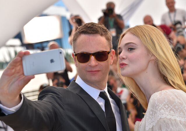 Danish director Nicolas Winding Refn (L) and US actress Elle Fanning pose for a selfie on May 20, 2016 during a photocall for the film The Neon Demon at the 69th Cannes Film Festival in Cannes, southern France.
