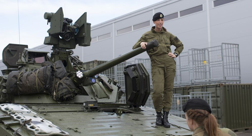 Female soldiers talk next to a CV90 combat vehicle at the armoured battalion in Setermoen, northern Norway on 11 August 2016. Norway was the first NATO member to have compulsory conscription for women as well as men in the army.