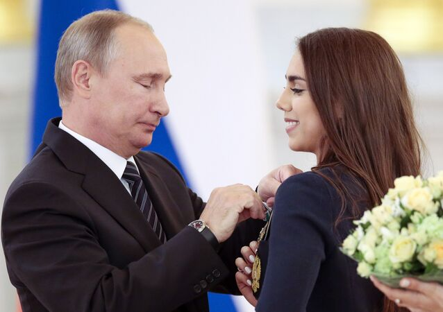 Russian President Vladimir Putin, left, gives an award to Margarita Mamun, who won the gold medal for rhythmic gymnastics individual, during an awarding ceremony for Russia's Olympians in Moscow's Kremlin in Moscow, Russia