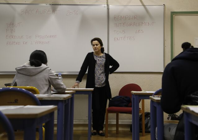 A teacher monitors (C) as High school students at the Charlemagne High School (Lycee Charlemagne) in Paris