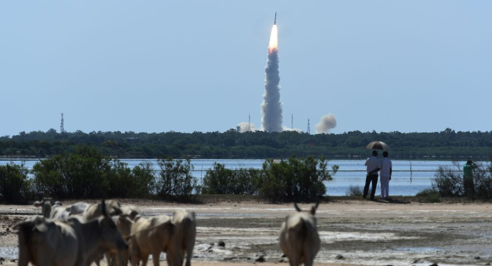 Bystanders watch as Indian Space Research Organisation's (ISRO) satellite CARTOSAT-2, along with 20 other satellites from the US, Canada, Germany and Indonesia on board the Polar Satellite Launch Vehicle (PSLV-C34), is launched from Sriharikota in the southern state of Andhra Pradesh on June 22, 2016