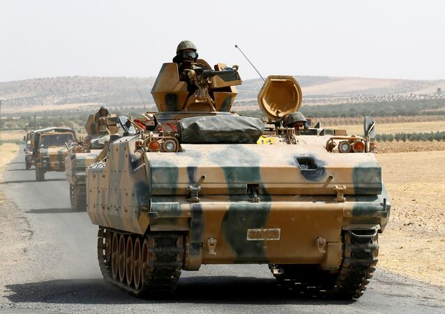 Turkish armoured personnel carriers escort military vehicles on a main road in Karkamis on the Turkish-Syrian border in the southeastern Gaziantep province, Turkey, August 26, 2016
