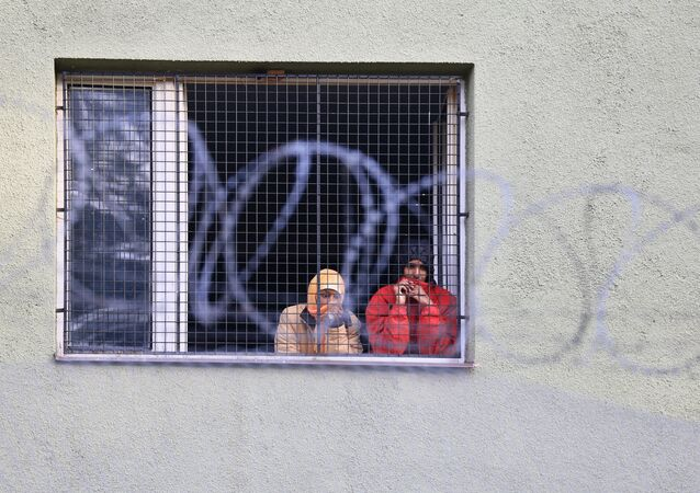 Migrants watch out of a window behind a fence at the Bela-Jezova detention centre for refugees near Bela pod Bezdezem, northeast of Prague (File)