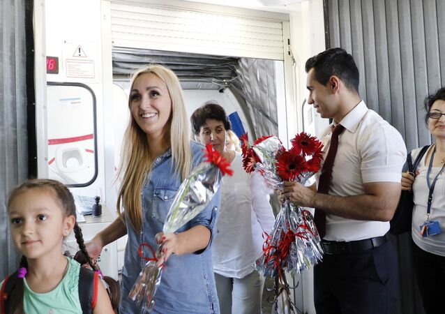 Turkish airport employees welcome Russian tourists after arriving on a charter flight on July 9, 2016 at an airport in Antalya